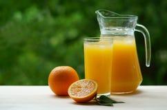 蒸馏瓶和一杯与冰的橙汁 库存图片
