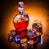 蒸馏瓶和两块玻璃用威士忌酒和冰 库存照片