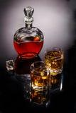 蒸馏瓶和两块玻璃用威士忌酒和冰 图库摄影