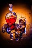 蒸馏瓶和两块玻璃用威士忌酒和冰 免版税图库摄影