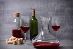 蒸馏瓶和玻璃用红葡萄酒在桌上 库存照片