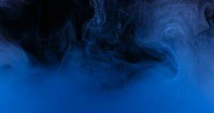蓝墨水颜色在创造液体艺术形状的水中 库存图片