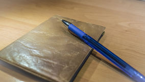 蓝墨水圆珠笔和文件在木书桌上 免版税库存图片