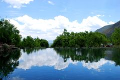 蓝天、白色云彩、纯净的水和绿色树 免版税图库摄影