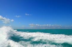 蓝天、白色云彩和青绿色波浪 库存照片