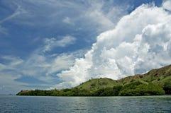 蓝天、空白云彩和绿色海岛 免版税库存照片