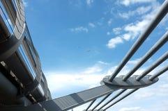 蓝天和一座桥梁有一只小风筝的和一架飞机在天空中 图库摄影