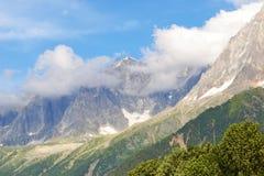 蓝天和云彩、象草的小山和落矶山 库存照片