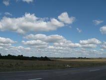 蓝天和云彩在领域 免版税库存照片