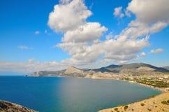蓝天和白色云彩在海湾上在黑海在克里米亚,海滩的在Sudak 免版税图库摄影