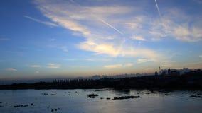 蓝天在一个早晨,太阳上升,看平面线,河 图库摄影