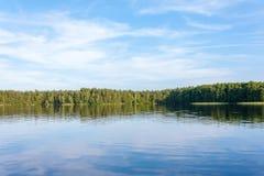 蓝天在Belarusian湖的干净的镜子表面被反射 免版税库存图片