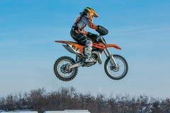 蓝天背景的高飞行摩托车竟赛者 图库摄影