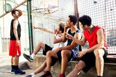 蓝球运动员休假坐低墙壁 免版税图库摄影