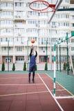 蓝球运动员在一个开放体育场投掷球入圆环 库存图片
