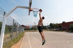 蓝球运动员是对灌篮 库存照片