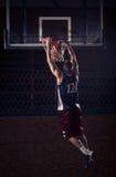 蓝球运动员灌篮,在空气 免版税库存照片