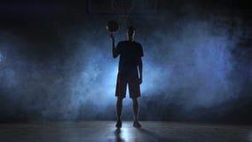 蓝球运动员转动的球,有泛光灯的黑暗的有薄雾的室接近的英尺长度在他的手指的 股票录像
