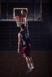 蓝球运动员,一手灌篮 免版税库存图片