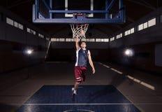 蓝球运动员,在空气,户内黑暗的篮球cou的灌篮 免版税库存照片