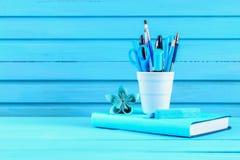 蓝皮书和文具在一张蓝色木桌上 教育,研究 免版税库存图片
