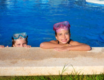 蓝眼睛儿童女孩蓝色池游泳池边微笑的 免版税库存照片