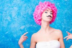 蓝眼睛可笑的女孩/妇女/少年有桃红色卷曲假发的是我们 免版税库存照片