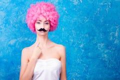 蓝眼睛可笑的女孩/妇女/少年有桃红色卷曲假发的是我们 图库摄影