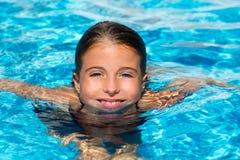 蓝眼睛在水中开玩笑女孩在池表面 库存照片