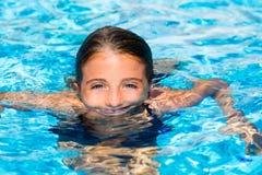 蓝眼睛在水中开玩笑女孩在池表面 库存图片