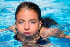 蓝眼睛在水中开玩笑女孩在池表面 免版税库存照片