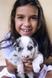 蓝眼睛的女孩藏品小狗 免版税库存照片