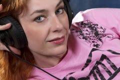 蓝眼睛的耳机妇女 免版税库存图片