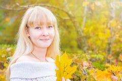 蓝眼睛的金发碧眼的女人在秋天公园 库存图片