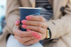 蓝纸咖啡在女性手上有桃红色修指甲的 库存照片