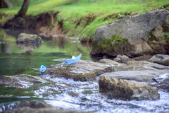 蓝纸在岩石的小船堆在与绿草的小河开户 库存照片