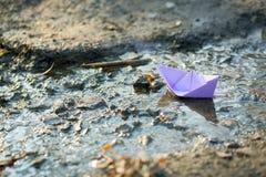 蓝纸小船在水中 免版税库存照片