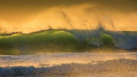 蓝绿色波浪在一个有风日落晚上打破 库存照片