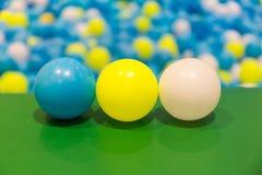 蓝色、黄色和白色三个五颜六色的球在球水池 图库摄影