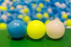 蓝色、黄色和白色3个球在儿童` s球挖坑 库存照片
