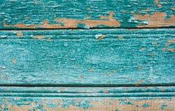 蓝色上色了在木纹理的破裂的油漆削皮 免版税库存照片