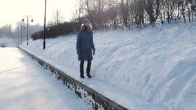 蓝色下来夹克的少妇沿边界在冬天公园和神色在天空,正面图走 股票视频