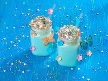 蓝色与被鞭打的奶油,糖和五颜六色的独角兽热巧克力洒,在一个蓝色木板的集合 库存照片