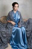蓝色丝绸礼服和鞋带长的海角的年轻浅黑肤色的男人坐葡萄酒沙发 免版税图库摄影