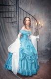 蓝色中世纪礼服的美丽的妇女有大烛台的 免版税库存图片