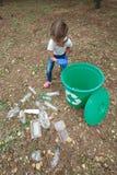 蓝色乳汁手套的孩子,投掷的塑料袋到回收站里 土地和垃圾在背景 免版税图库摄影