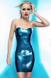 蓝色乳汁礼服的白肤金发的妇女 免版税库存照片