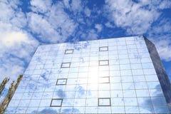 蓝色云彩和树在杯被反射一个现代大厦的窗口 底视图 免版税库存照片