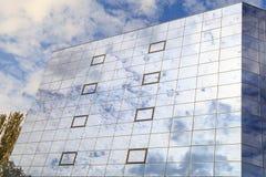 蓝色云彩和树在杯被反射一个现代大厦的窗口 正确的看法 免版税库存照片