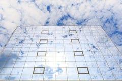 蓝色云彩在杯被反射一个现代大厦的窗口 底视图 免版税库存照片